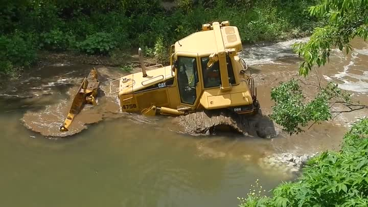 Skilled machine operator removes his CAT D6N from creek